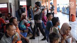 Pasukan Brimob Polda Metro Jaya bersenjata berjalan di antara penumpang di Terminal Kampung Rambutan, Jakarta, Selasa (19/6). Penjagaan dilakukan untuk memberi rasa aman kepada pemudik pada arus balik Lebaran 2018. (Liputan6.com/Faizal Fanani)
