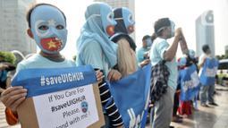 Warga mengenakan topeng bendera Turkestan Timur dan membentangkan poster saat menggelar Aksi Save Uighur selama Hari Bebas Kendaraan Bermotor (HBKB) atau Car Free Day (CFD), Jakarta, Minggu (22/12/2019). (merdeka.com/Iqbal S. Nugroho)