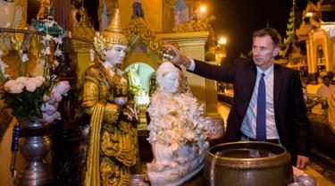 Menteri Luar Negeri Inggris, Jeremy Hunt menuangkan air ke patung Buddha ketika mengunjungi Pagoda Shwedagon di Yangon, Myanmar. Rabu (19/9). Hunt tiba di Myanmar untuk mengunjungi pusat krisis Rohingya dan menemui Aung San Suu Kyi. (AP/ Ye Aung Thu)