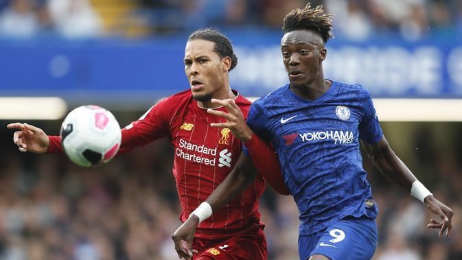 Bek Liverpool, Virgil van Dijk (kiri) berebut bola dengan penyerang Chelsea, Tammy Abraham selama pertandingan lanjutan Liga Inggris di Stadion Stamford Bridge, London (22/9/2019). Liverpool menang tipis atas Chelsea 2-1. (AP Photo/Frank Augstein)