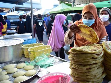 Seorang pedagang membuat roti di pasar makanan pada hari pertama bulan suci Ramadhan di provinsi Narathiwat di Thailand selatan (24/4/2020). Sejumlah pedagang menjual berbagai makanan selama bulan suci Ramadan di pasar tersebut. (AFP/Madaree Tohlala)