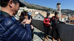 Wisatawan berfoto di benteng kota tua Dubrovnik di Kroasia pada 28 Maret 2019. Kota tua Dubrovnik  yang telah dianugerahi UNESCO sebagai warisan dunia menjadi salah satu hal yang menjadi daya tarik wisatawan untuk terbang atau berlayar ke kota yang dikelilingi pulau ini. (Denis LOVROVIC / AFP)