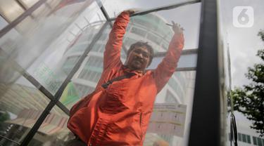 Warga masuk dalam ruang khusus semprot Desinfektan Chamber di depan Pasar Raya Blok M, Jakarta, Selasa (24/3/2020). Pamasangan ruang khusus semprot Desinfektan Chamber untuk mensterilkan full body masyarakat untuk menekan penyebaran Covid-19. (Liputan6.com/Faizal Fanani)