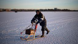 Seorang pria usai memancing di laut Bothnia yang sedang membeku, Vaasa, Finlandia (29/12). Kebiasaan memancing di laut beku merupakan hal menantang yang ditunggu-tunggu oleh sebagian warga setempat. (AFP PHOTO/Olivier Morin)