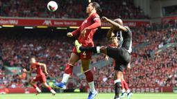 Bek Liverpool, Virgil Van Dijk, berebut bola dengan bek Newcastle, Jetro Willems, pada laga Premier League di Stadion Anfield, Liverpool, Sabtu (14/9). Liverpool menang 3-1 atas Newcastle. (AFP/Paul Ellis)