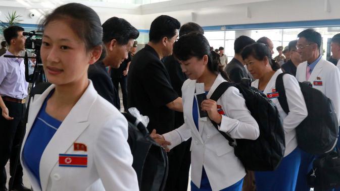 Atlet Korea Utara yang dikepalai Wakil Menteri Olahraga Korea Utara, Won Kil U bersiap meninggalkan bandara internasional Pyongyang, Korut (10/8). Korut akan berpartisipasi dalam Asian Games 2018 di Jakarta dan Palembang, Indonesia. (AP Photo/Cha Song Ho)