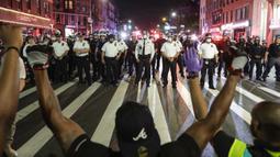 Para pengunjuk rasa berlutut di Flatbush Avenue di depan petugas kepolisian Kota New York selama unjuk rasa untuk George Floyd di wilayah Brooklyn di New York, AS (4/6/2020). (AP Photo/Frank Franklin II)