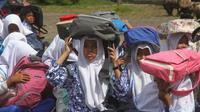 Para murid menggunakan tas untuk pelindung dalam latihan tsunami di Meulaboh (5/9). Sebanyak 24 negara yang berbatasan dengan Samudra Hindia, dari Australia hingga Yaman, mengambil bagian dalam latihan kesiapsiagaan bencana dua tahunan. (AFP Photo/Januar)