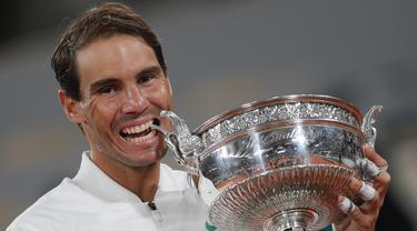 Petenis Rafael Nadal menggigit trofi saat merayakan kemenangannya atas Novak Djokovic pada final Prancis Terbuka 2020 di Stadion Roland Garros, Paris, Prancis, Minggu (11/10/2020). Dengan kemenangan ini, Nadal menyamai rekor Roger Federer dengan meraih 20 gelar Grand Slam. (AP Photo/Michel Euler)