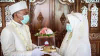 Pasangan pengantin usai melaksanakan prosesi akad nikah di KUA Jagakarsa, Jakarta, Sabtu (6/6/2020). Pernikahan mengikuti protokol kesehatan sesuai Surat Edaran (SE) Menteri Agama Nomor 15 Tahun 2020. (Liputan6.com/Faizal Fanani)