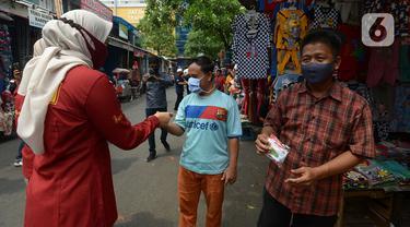 Petugas membagikan masker kepada warga di Pasar Jatinegara, Kamis (10/9/2020). Petugas gabungan terus melakukan himbauan untuk memakai masker dan membagikan masker di pasar tersebut. (merdeka.com/Imam Buhori)