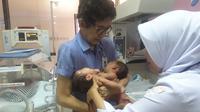 Ketua tim dokter penanganan bayi kembar siam RSHS Dadang Sjarief Hidajat, tengah melakukan pemeriksaan terhadap bayi kembar dempet dada dan perut asal Cirebon, di Bandung, Jumat, 23 November 2018 lalu. (Sumber foto: Prof. Dadang Sjarief Hidajat)