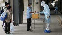 Petugas kesehatan memeriksa kadar oksigen pasien COVID-19 setibanya di Stasiun Rangsit, Provinsi Pathum Thani, Thailand, Selasa (27/7/2021). Pengiriman pasien COVID-19 dari Bangkok ke kota asal mereka ini untuk meringankan beban sistem medis ibu kota yang kewalahan. (AP Photo/Sakchai Lalit)