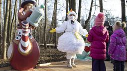 """Seorang pemandu wisata yang mengenakan kostum karakter dongeng Rusia, Putri Salju, mengobrol dengan anak-anak dalam pembukaan """"Jalur Dongeng"""" di """"Kediaman Kakek Frost"""" di Moskow, Rusia (18/11/2020). (Xinhua/Alexander Zemlianichenko Jr)"""