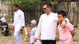 Presenter Eko Patrio ditemanin putranya melihat proses pemotongan hewan kurban di kawasan Cipinang, Jakarta, Jumat (1/9). Khusus di kantornya, Eko berkurban dua ekor sapi dan tiga ekor kambing. (Liputan6.com/Herman Zakharia)