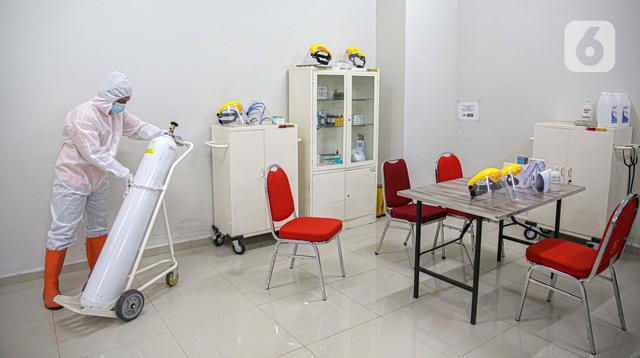 Petugas mengenakan hazmat saat menyiapkan tabung oksigen di Tower 8 Wisma Atlet Pademangan, Jakarta, Selasa (15/6/2021). Tower 8 Wisma Atlet Pademangan bisa menampung 1.569 pasien untuk isolasi. (Liputan6.com/Faizal Fanani)