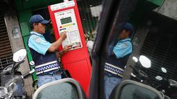 Petugas melakukan pembayaran pada mesin parkir meter di Jalan Falatehan, Jakarta, Selasa (1/11). Melalui mesin parkir meter, pemerintah mendorong penggunaan uang elektronik, khususnya untuk sektor transportasi. (Liputan6.com/Immanuel Antonius)