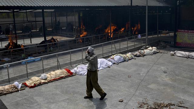 Seorang pria berjalan melewati barisan jasad korban virus corona COVID-19 yang akan dikremasi di tempat kremasi di New Delhi, India, Rabu (28/4/2021). Sekitar 117 orang India meninggal karena COVID-19 setiap satu jam. (Money SHARMA/AFP)
