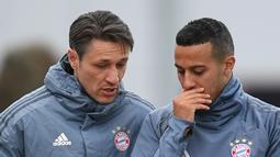 Pelatih Bayern Munchen, Niko Kovac (kiri) berbincang dengan gelandang Thiago Alcantara selama sesi latihan tim di Munich, Jerman selatan (12/3). Pada leg pertama Munchen berhasil menahan imbang Liverpool 0-0 di Anfield Stadium. (AFP Photo/Christof Stache)