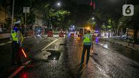 Polisi berjaga saat penyekatan jalan di kawasan Pasar Baru, Jakarta, Kamis (31/12/2020). Polda Metro Jaya menutup sejumlah ruas jalan selama Car Free Night dan Crowd Free Night pada malam Tahun Baru 2021 untuk mencegah penyebaran COVID-19. (Liputan6.com/Faizal Fanani)