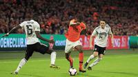 Pemain Belanda, Denzel Dumfries, berusaha melewati bek Jerman, Antonio Rudiger, pada laga kualifikasi Piala Eropa di Stadion Johan Cruyff, Minggu (24/3). Belanda takluk 2-3 dari Jerman. (AP/Peter Dejong)