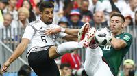 Gelandang Jerman, Sami Khedira, berebut bola dengan bek Meksiko, Hector Herrera, pada laga Grup F Piala Dunia di Stadion Luzhniki, Moskow, Minggu (17/6/2018). Meksiko menang 1-0 atas Jerman. (AP/Matthias Schrader)