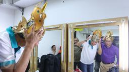 Gubernur Jawa Tengah Ganjar Pranowo (kaos putih) dan Dirut BTN Maryono (kemeja ungu) saat mencoba mahkota di ruang ganti sebelum pementasan ketoprak dengan tema Menyatukan Kembali Nusantara di GKJ, Jakarta, Minggu (21/8). (Liputan6.com/Angga Yuniar)