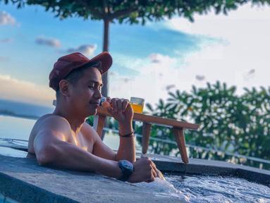 Aktor kelahiran 9 Februari 1988 ini memang kerap kali menikmati liburan di pantai. Seperti foto ini yang memperlihatkan Ajun tengah berendam sambil menikmati segelas minuman. Dengan background disekelilingnya laut, membuat Ajun begitu menikmati liburannya. (Liputan6.com/IG/@ajunperwira)