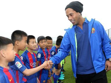 Mantan pemain Barcelona, Ronaldinho, menyalami anak-anak saat peluncuran akademi sepak bola Barcelona di China, Jumat (24/2/2017). (AFP/Handout)
