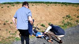 Petugas memberikan pertolongan kepada pembalap sepeda Belgia, Michael Goolaerts setelah terjatuh pada balapan klasik Paris-Roubaix di Prancis Utara, Minggu (8/4). Goolaerts jatuh di sektor kedua dari balapan sejauh 257 km. (DAVID STOCKMAN/Belga/AFP)