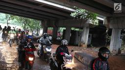Pengendara motor melintasi jalan setapak di kolong tol di kawasan Lebak Bulus, Jakarta, Selasa (13/2). Untuk menghindari macet sebagian pengendara memanfaatkan jalan setapak tersebut untuk memersingkat waktu tempuh. (Liputan6.com/Immanuel Antonius)
