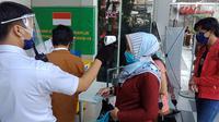 Petugas keamanan di pusat perbelanjaan Bandung Electronic Center memeriksa suhu pengunjung sebagai salah satu protap kesehatan pencegahan Covid-19. (Liputan6.com/Huyogo Simbolon)