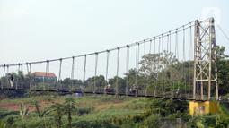 Suasana jembatan gantung di Kelurahan Curug, Bojongsari, Kota Depok, Jawa Barat, Senin (24/8/2020). Setiap sore, warga sekitar bermain di jembatan tersebut sambil menikmati matahari tenggelam. (merdeka.com/Dwi Narwoko)