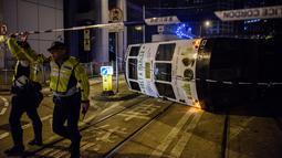 Petugas kepolisian memblokir lokasi sebuah trem double-decker yang terbalik di jalan utama di Hong Kong, Kamis (6/4). Hong Kong telah mengoperasikan tram, yang dikenal sebagai 'ding-ding' lebih dari satu abad lalu. (ANTHONY WALLACE/AFP)