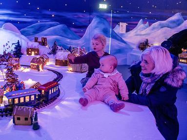 Seorang ibu dan anak-anaknya melihat pameran desa jahe di Bergen, Norwegia pada 18 November 2019. Pameran tahunan yang populer ini menampilkan ratusan rumah dan struktur lainnya dari kue jahe yang identik dengan perayaan Natal. (Marit Hommedal / NTB Scanpix / AFP)