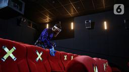 Pekerja membersihkan bangku bioskop Cinepolis di Jakarta Jumat (23/10/2020). Sejumlah bioskop di Ibu kota kembali beroperasi setelah mendapatkan izin dari Pemprov DKI Jakarta dengan jumlah penonton dibatasi maksimal 25 persen dari total kapasitas. (Liputan6.com/Faizal Fanani)