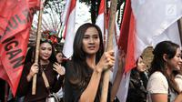 Sejumlah wanita membawa bendera saat memeriahkan arak-arakan PDIP menuju Kantor KPU, Jakarta, Selasa (17/7). Kedatangan anggota PDIP untuk mendaftarkan bakal caleg di KPU diiringi pawai bendera, ondel-ondel, musik. (Merdeka.com/Iqbal S. Nugroho)