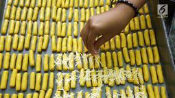 Adonan kue kering ditaburi keju saat proses pembuatan di industri rumahan kawasan Kwitang, Jakarta, Sabtu (18/5/2019). Jelang Lebaran, pengusaha kue kering rumahan mulai kebanjiran pesanan. (Liputan6.com/Herman Zakharia)