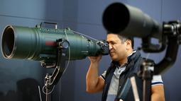 Pengunjung mencoba mengoperasikan lensa supertele Sigma pada stand Kamera Sigma saat berlangsungnya Pameran Photokina di Cologne, Jerman, (20/9). Pameran Photokina pertama diadakan di Cologne, Jerman, pada tahun 1950. (REUTERS/Fabrizio Bensch)