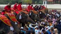 Sejumlah warga mengantri memberikan makanan pada gajah dalam acara Hari Nasional Gajah Thailand di Ayutthaya, Jumat (13/3/2015). Acara ini dilakukan untuk memberi penghormatan pada gajah. (REUTERS/Athit Perawongmetha)