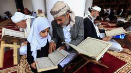 Seorang pria membaca Al-Quran bersama putrinya selama bulan Ramadan di Masjid Agung Sanaa, Yaman, Minggu (26/4/2020). Masjid Agung Sanaa bagian dari Situs Warisan Dunia UNESCO. (Mohammed HUWAIS/AFP)