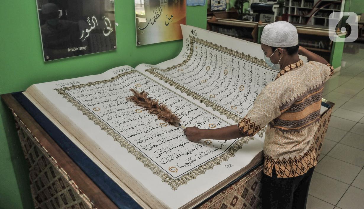 Petugas membersihkan Alquran raksasa koleksi Perpustakaan Jakarta Islamic Center (JIC), Jakarta Utara, Kamis (22/4/2021). Alquran raksasa tersebut merupakan pemberian dari Universitas Sains Alquran Wonosobo sebagai penghargaan atas berdirinya masjid JIC pada 2002. (merdeka.com/Iqbal S Nugroho)