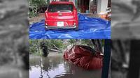Mobil terpaksa dibungkus agar air tidak masuk ke dalam mobil (acidcow)