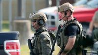 Polisi dengan peralatan taktis bersiaga usai penembakan di Santa Fe High School, Texas, AS, Jumat (18/5). Gubernur Texas Greg Abbot mengatakan tersangka menggunakan senapan dan pistol kaliber 38. (Kevin M. Cox/The Galveston County Daily News via AP)