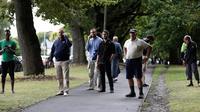 Warga menunggu dekat lokasi penembakan di Masjid Al Noor, Christchurch, Selandia Baru, Jumat (15/3). Polisi masih menyisir lokasi kejadian dan mengosokan seluruh ruas jalan Deans Avenue. (AP Photo/Mark Baker)