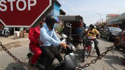 Orang-orang diblokir oleh petugas polisi setempat untuk masuk ke jalan kota utama dekat bandara Internasional Phnom Penh di Phnom Penh, Kamis (15/4/2021). Pemimpin Kamboja memutuskan untuk lockdown Phnom Penh selama dua minggu menyusul kenaikan tajam kasus COVID-19. (AP Photo/Heng Sinith)