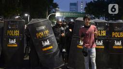 Seorang pendemo foto bersama anggota kepolisian saat aksi menolak Omnibus Law UU Cipta Kerja di kawasan Patung Kuda, Jakarta, Selasa (20/10/2020).  Anggota Marinir membubarkan dan mengawal pulang massa pendemo  ke rumah masing-masing. (merdeka.com/Imam Buhori)
