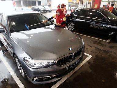Petugas membersihkan kaca saat pengisian BBM Shell V-Power ke mobil BMW 520i Luxury dalam acara flag off di SPBU Shell Gatot Subroto, Jakarta, Senin (12/3). Program BMW Driving Experience adalah kegiatan menempuh lima kota besar. (Merdeka.com/Dwi Narwoko)