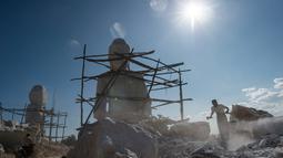 Seorang pria memecahkan batu di dekat patung Buddha di desa Sagyin, Madaya, Myanmar pada 22 Desember 2018.  Patung-patung marmer yang diproduksi di desa Sagyin ini diekspor ke Thailand, Vietnam, dan Taiwan. (YE AUNG THU / AFP)