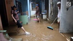 Pemandangan saat warga membersihkan rumah mereka akibat banjir yang melanda Kampung Melayu, Jakarta Timur, Senin (25/6). Air mulai merendam rumah warga sekitar pukul 04.00 WIB. (Liputan6.com/Arya Manggala)